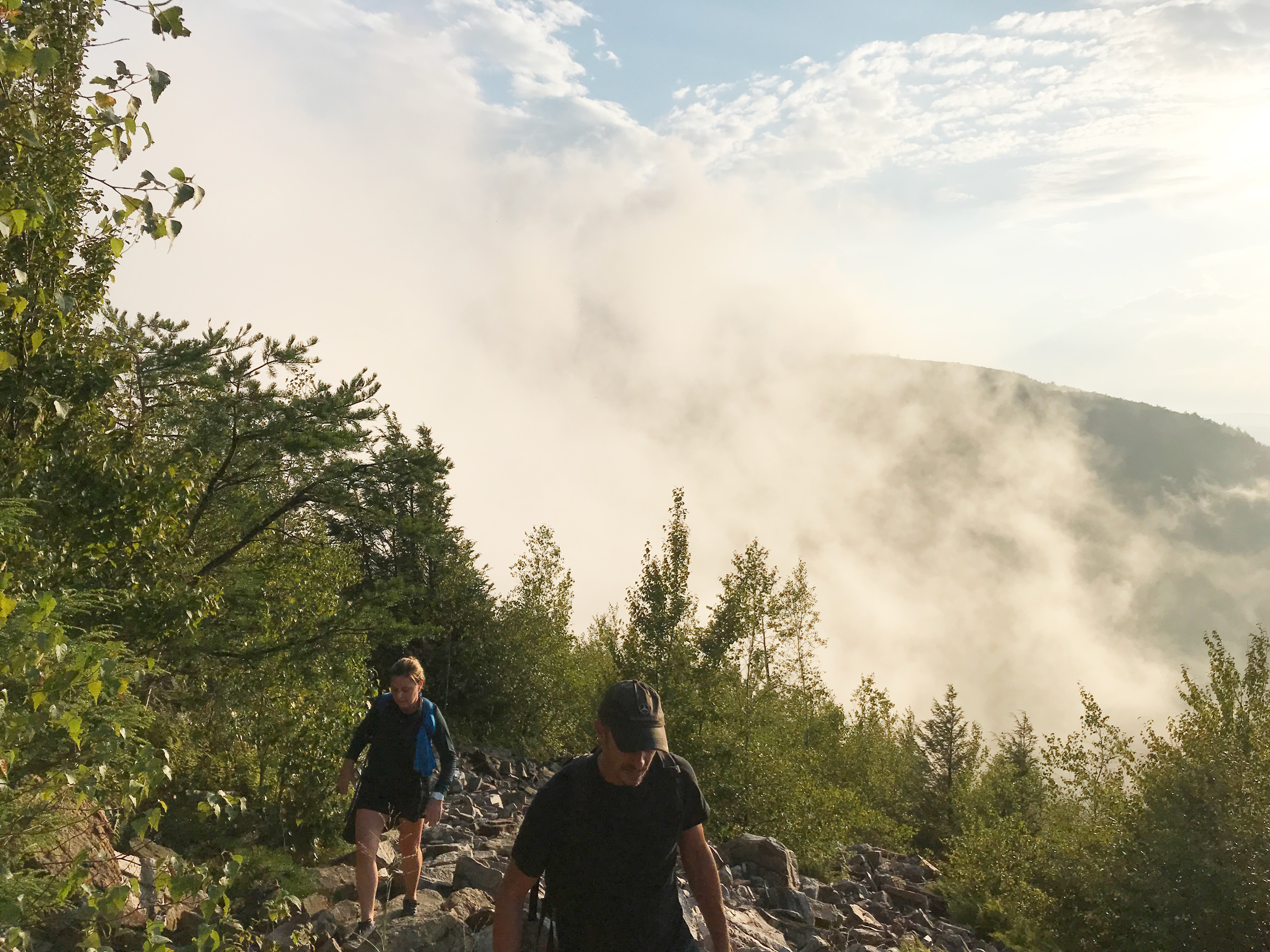 A group hiking with clouds in the background