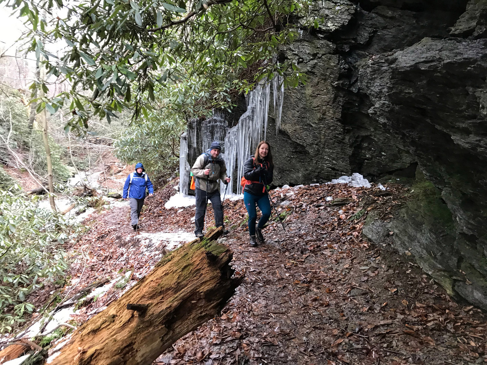 hikers hike past trail icicles