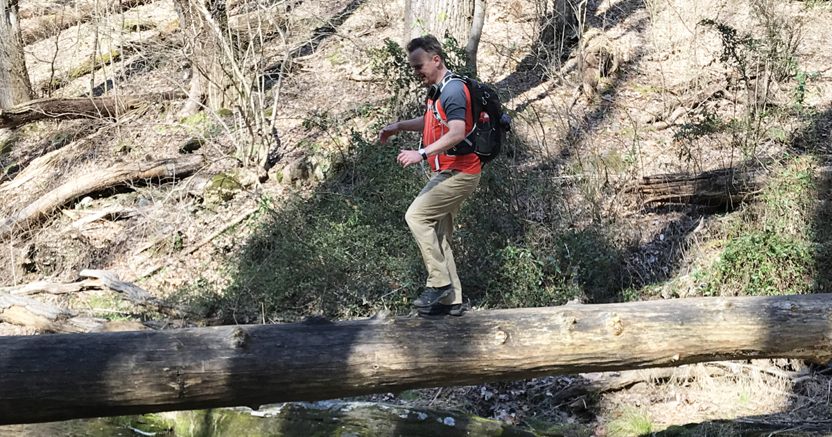 hiker-crosses-stream-by-with-a-log